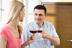 Pares que tuestan las copas de vino rojas en cocina Imagenes de archivo