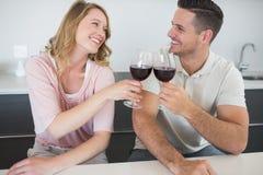 Pares que tuestan las copas de vino rojas en la tabla Fotos de archivo libres de regalías