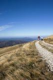Pares que van de excursión en una montaña imagenes de archivo