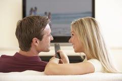 Pares que ven la TV con pantalla grande en casa Imagen de archivo libre de regalías