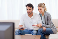 Pares que ven la TV mientras que come las palomitas Imagen de archivo