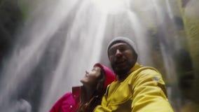 Pares que viajan felices jovenes que toman un selfie en cámara del gopro Hombre y mujer cerca de la cascada de Gljufrabui en Isla almacen de metraje de vídeo
