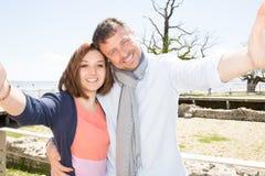 pares que viajan que hacen que el selfie vara el fondo, colores soleados del verano, humor romántico Imagen de archivo