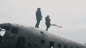 Pares que viajan jovenes que caminan en el top del avión estrellado DC-3 en Islandia en el día cubierto ventoso almacen de metraje de vídeo