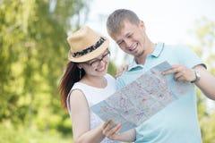 Pares que viajan sonrientes que miran el mapa Fotografía de archivo libre de regalías