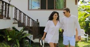 Pares que vienen abajo de casa del chalet tener un paseo en el jardín tropical, el hombre feliz y la mujer abrazando charla al ai almacen de metraje de vídeo
