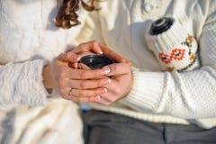 pares queridos jovenes que se calientan en el parque del invierno manos con las tazas de té caliente Fotografía de archivo libre de regalías