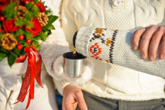 pares queridos jovenes que se calientan en el parque del invierno manos con las tazas de té caliente Foto de archivo libre de regalías