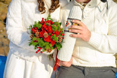 pares queridos jovenes que se calientan en el parque del invierno manos con las tazas de té caliente Fotos de archivo