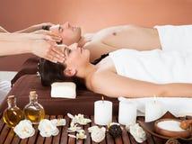 Pares relajados que reciben el masaje principal en el balneario Foto de archivo libre de regalías