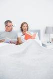 Pares relajados que se sientan en libros de lectura de la cama Foto de archivo