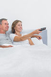 Pares relajados que ven la TV en cama Fotos de archivo libres de regalías