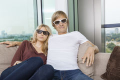 Pares relaxado que vestem os vidros 3D ao sentar-se no sofá em casa Fotos de Stock Royalty Free