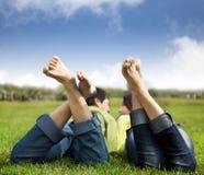 Pares Relaxed que encontram-se no verde Fotos de Stock Royalty Free