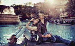 Pares Relaxed que se reclinan en la ciudad Foto de archivo