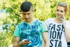 Pares reservados con los teléfonos elegantes en sus manos - el par joven tiene problemas de la privacidad con tecnología moderna Fotos de archivo