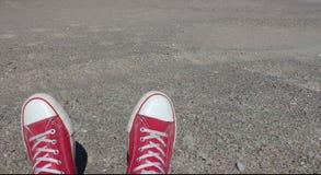 Pares rojos de zapatillas de deporte gastadas en la arena de la playa en día de verano Imagenes de archivo