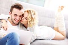 Pares románticos con el ordenador portátil en sala de estar foto de archivo libre de regalías