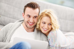 Pares románticos con el ordenador portátil en sala de estar fotografía de archivo libre de regalías