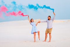 pares románticos con la bomba de humo del color azul y del color rojo en la playa Fotografía de archivo