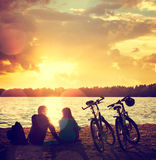 Pares románticos con las bicis por el lago Imagenes de archivo