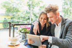 Pares románticos con una tableta en el café en un fondo borroso Concepto romántico Copie el espacio Imagenes de archivo