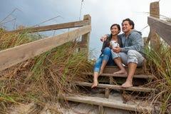 Pares románticos de la mujer asiática del hombre en pasos de la playa imagen de archivo libre de regalías