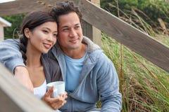 Pares románticos de la mujer asiática del hombre en pasos de la playa foto de archivo