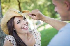 Pares románticos de la raza mixta con el vaquero Hat Flirting en parque Imagenes de archivo