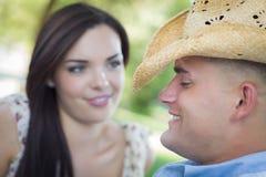 Pares románticos de la raza mixta de la diversión en el vaquero Hat Flirt en parque Imagenes de archivo