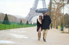 Pares románticos debajo de la lluvia en París Foto de archivo