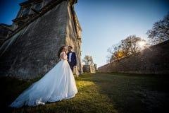 Pares románticos del cuento de hadas de los recienes casados que presentan en la puesta del sol cerca de castillo barroco viejo Imagen de archivo