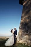 Pares románticos del cuento de hadas de los recienes casados que presentan en la puesta del sol cerca de viejo Foto de archivo libre de regalías