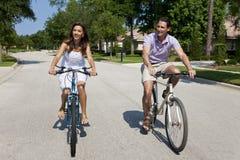 Pares románticos del hombre y de la mujer que completan un ciclo junto foto de archivo