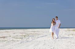 Pares románticos del hombre y de la mujer que recorren en una playa Fotos de archivo