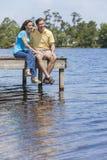 Pares románticos del hombre y de la mujer que se sientan por Lake Foto de archivo libre de regalías