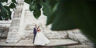 Pares románticos del recién casado que presentan junto cerca de la pared vieja del castillo adentro Imagen de archivo