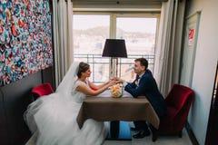 Pares románticos del recién casado que se sientan junto en restaurante en la tabla para dos con el ramo nupcial de rosas que pone Imagen de archivo