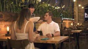 Pares románticos dinning en la igualación del restaurante Pares jovenes de la porción de la camarera mientras que fecha en café e almacen de metraje de vídeo