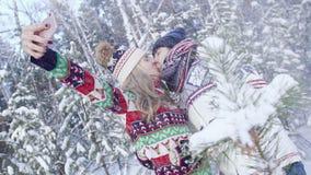 Pares románticos en el bosque nevoso que besa y que toma el selfie almacen de metraje de vídeo