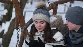 Pares románticos en el oscilación en parque del invierno almacen de video