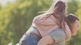 Pares románticos en el parque en el verano La muchacha salta al individuo en la parte posterior feliz junto metrajes