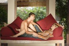 Pares románticos en el sofá rojo el vacaciones. Imágenes de archivo libres de regalías