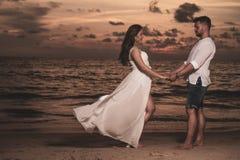 Pares románticos en la playa del th durante puesta del sol Imágenes de archivo libres de regalías