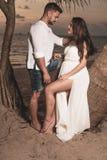 Pares románticos en la playa durante puesta del sol Fotos de archivo