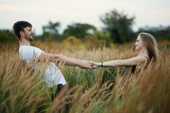 Pares románticos en la puesta del sol Dos personas en amor en la puesta del sol o la salida del sol Hombre y mujer en campo Fotografía de archivo libre de regalías