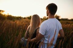 Pares románticos en la puesta del sol Dos personas en amor en la puesta del sol o la salida del sol Hombre y mujer en campo Fotos de archivo libres de regalías