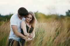 Pares románticos en la puesta del sol Dos personas en amor en la puesta del sol o la salida del sol Hombre y mujer en campo Foto de archivo libre de regalías