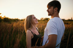 Pares románticos en la puesta del sol Dos personas en amor en la puesta del sol o la salida del sol Hombre y mujer en campo Fotos de archivo