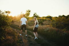 Pares románticos en la puesta del sol Dos personas en amor en la puesta del sol o la salida del sol Hombre y mujer en campo Imagen de archivo libre de regalías